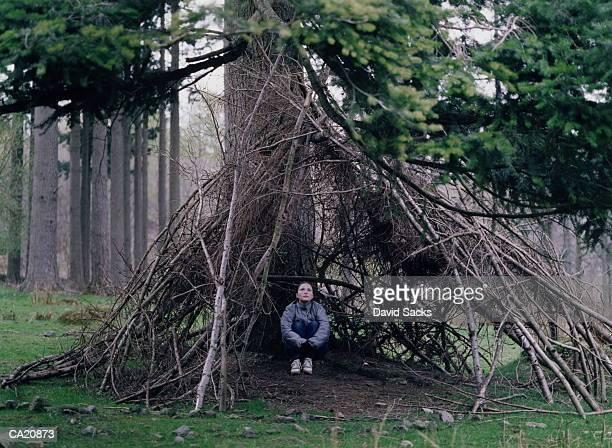 Teenage girl (13-15) sitting in bivouac in wood