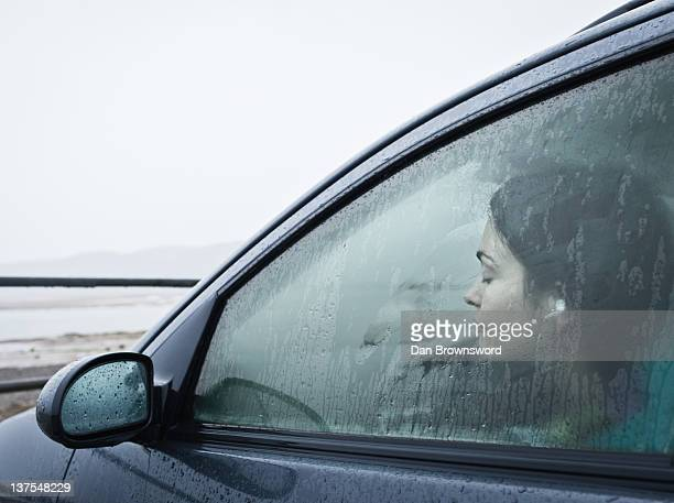 Teenage girl sitting in car by beach