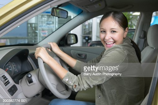 Teenage girl (17-19) sitting in car, hands on wheel, smiling, portrait : Stock Photo