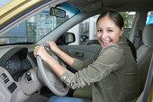 Teenage girl (17-19) sitting in car, hands on wheel, smiling, portrait