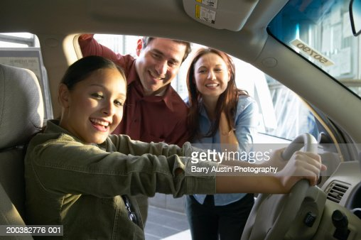 Teenage girl (17-19) sitting in car, parents in background, portrait : Stock Photo
