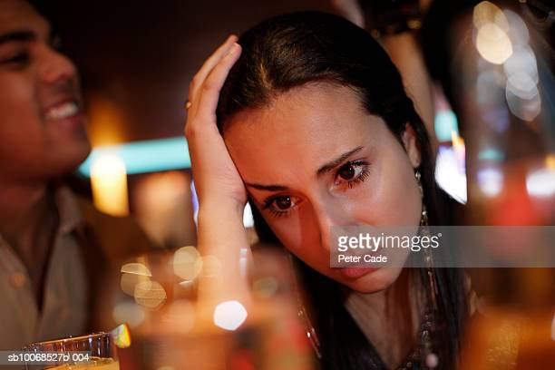Teenage girl (16-17) sitting in pub with head in hand