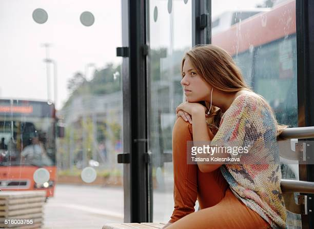 Teenage girl sitting on a bus stop