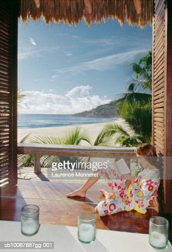 Teenage girl (13-14) sitting on floor reading book, beach in background, side view : Stock Photo