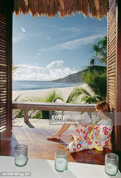 Teenage girl (13-14) sitting on floor reading book, beach in background, side view
