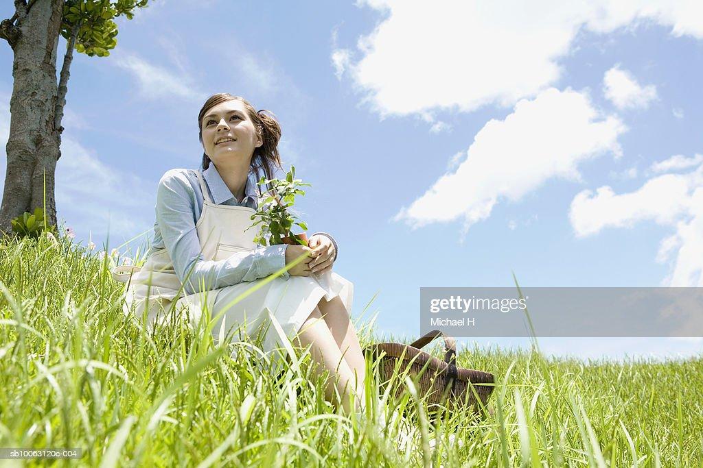 Teenage girl (16-17) sitting on grass, low angle view
