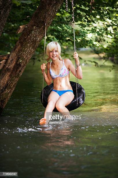 Teenage girl (13-15) sitting on hoop at river, smiling