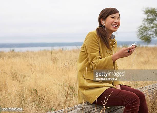 Teenage girl (15-17) sitting on log, listening to MP3 player, laughing