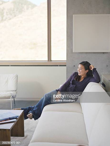 Teenage girl (16-18) sitting on sofa, smiling, side view