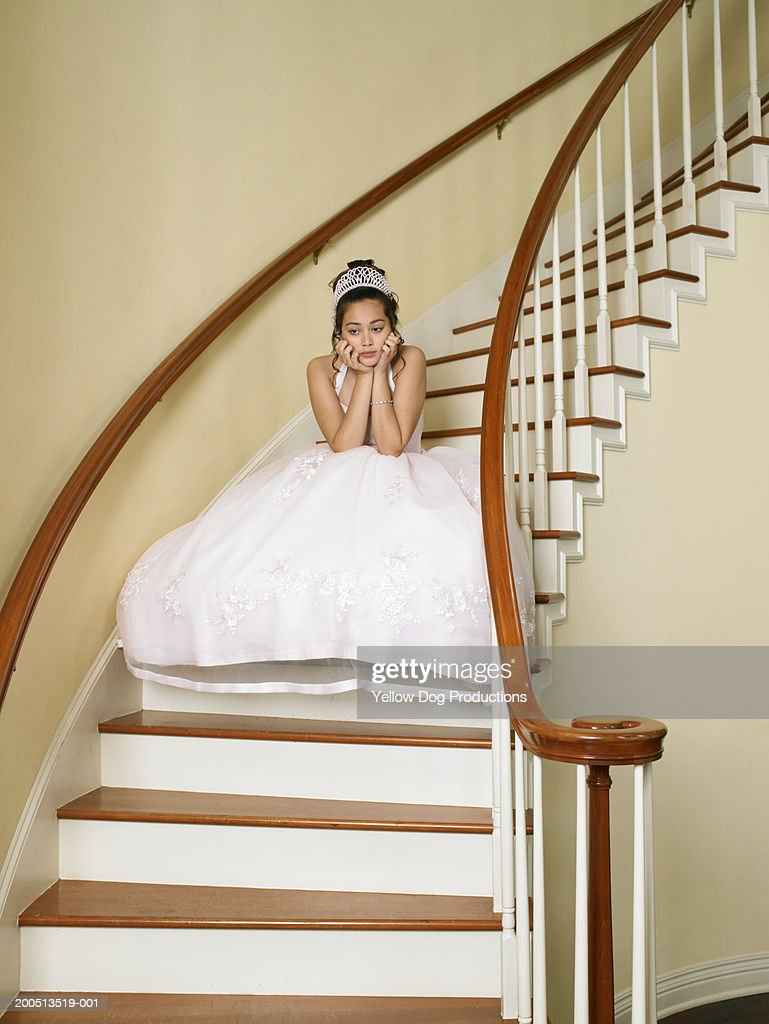 Teenage girl (14-16) sitting on stairway, wearing dress and tiara : Stock Photo
