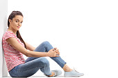 Teenage girl sitting on the floor and leaning against a wall isolated on white background