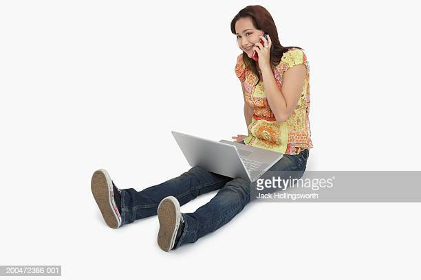Teenage girl sitting on the floor and talking on a mobile phone with a laptop on her lap