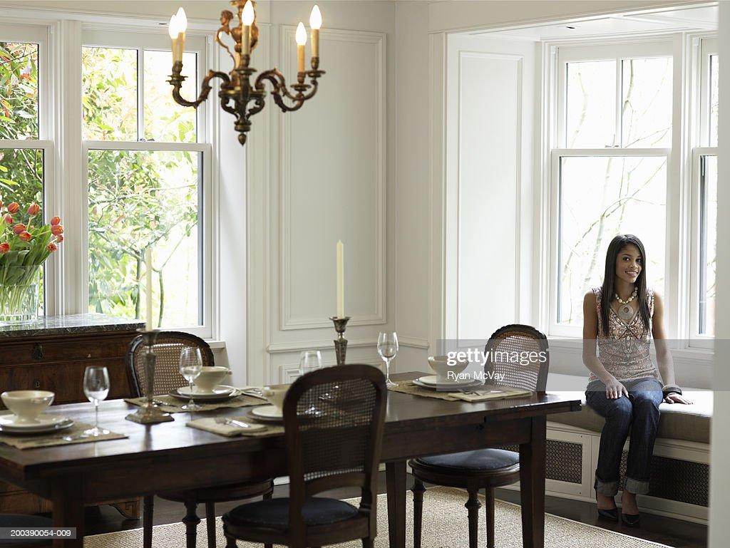 Teenage girl sitting on window seat in dining room for Window seat dining