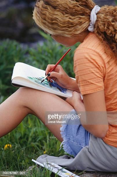 Teenage girl (16-17) sitting painting in field