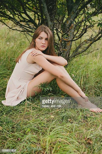 Teenage girl (14-15) sitting under tree