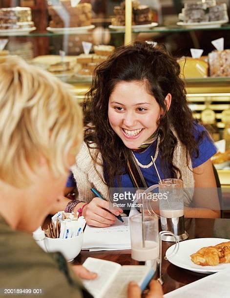 Teenage girl (15-17) sitting with teenage boy (16-18) in cafe, smiling