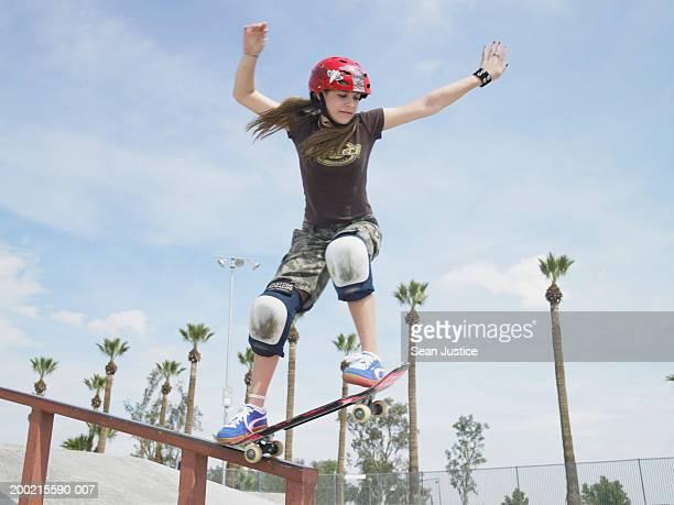 Teenage girl (14-16) skateboarding down rail