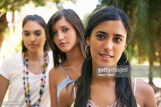 Teenage girl (16-18) smiling, portrait, young women in background