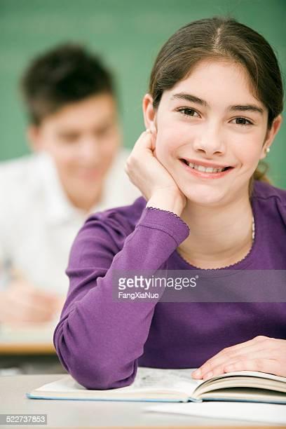 Teenager Mädchen lächelnd mit ein offenes Buch auf dem Schreibtisch