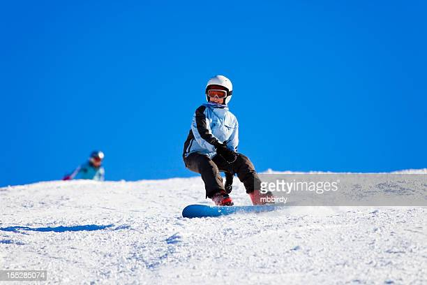 Teenage girl snowboarding on sunny winter day