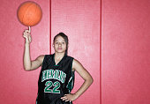 Teenage girl spinning a basketball on her finger on a basketball court