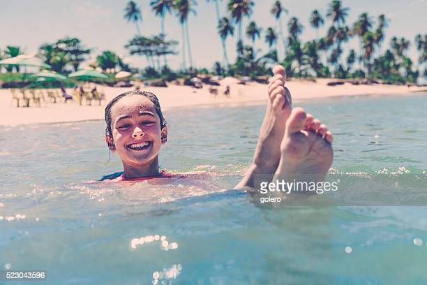 teenage girl splashing in brazilian tropic sea