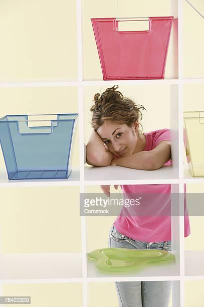 Teenage girl standing behind shelving cubes