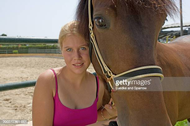 Teenage girl (16-18) standing by horse, smiling, portrait