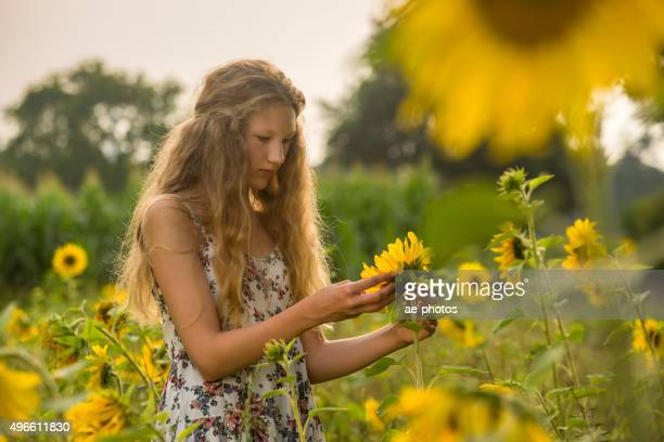 Teenage girl standing in a field of sunflowers