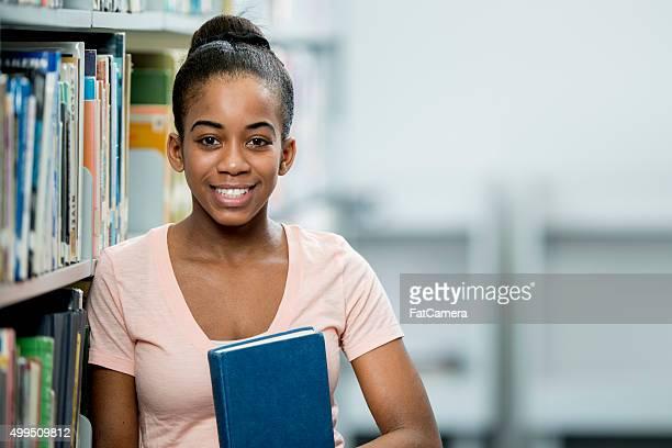 Teenager-Mädchen, stehend in der Bibliothek
