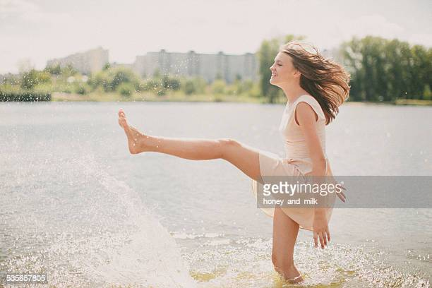 Teenage girl standing in a river kicking water