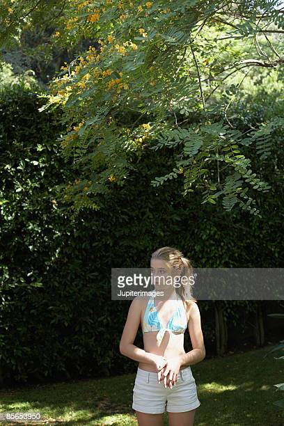 Teenage girl standing in backyard