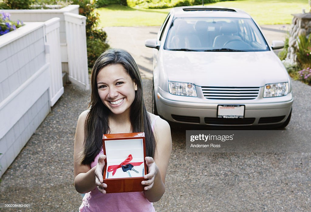 Teenage girl (14-16) standing in driveway, holding car keys with bow : Stock Photo