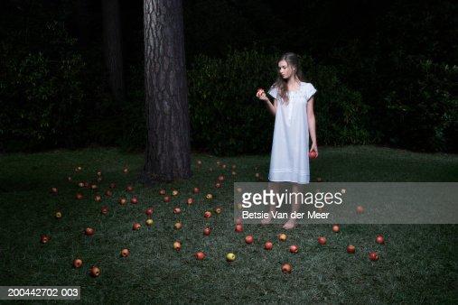 Teenage girl (16-18) standing in garden holding apple, night : Stock Photo