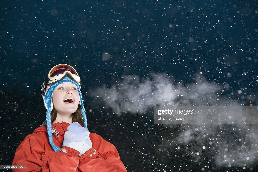 Teenage girl (15-17) standing in snow, smiling, night