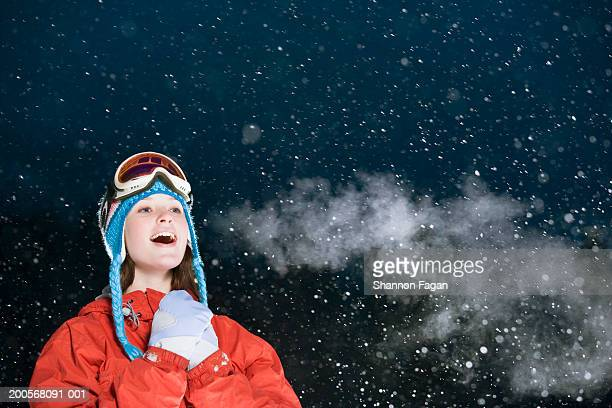 Teenage girl (15-17) standing in snow, smiling, night