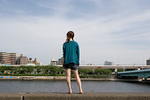 Teenage girl (18-20) standing on edge of river, rear view