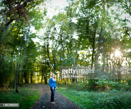 Teenage girl standing on path in woods : Stock Photo