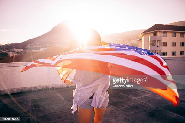 Teenage girl standing with an American flag on rooftop