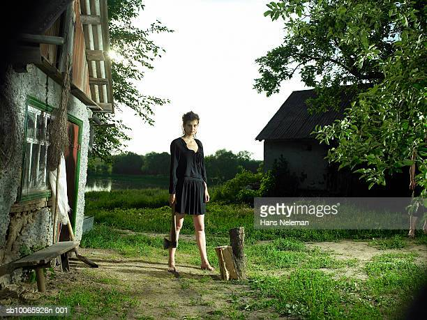 Teenage girl (16-17) standing with axe in farm, portrait