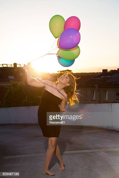 Teenage girl standing with balloons outdoors