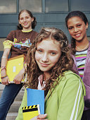 Teenage girl (13-15) standing with friends, smiling, portrait