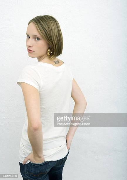 Teenage girl standing with hands in back pockets, looking over shoulder at camera, rear view