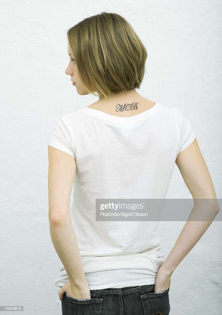 Teenage girl standing with hands in back pockets, rear view, portrait : Stock Photo