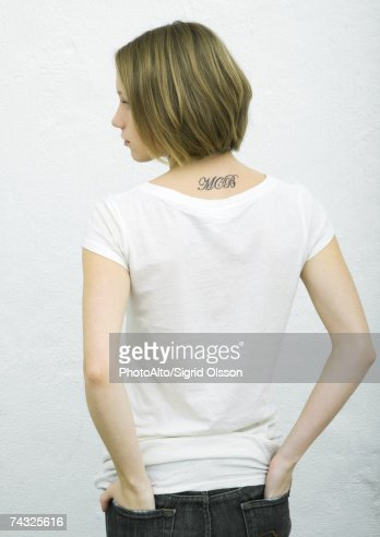 Teenage girl standing with hands in back pockets, rear view, portrait