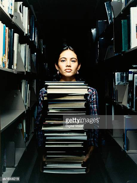 Teenage Girl Stands in a Library With a Large Stack of Books