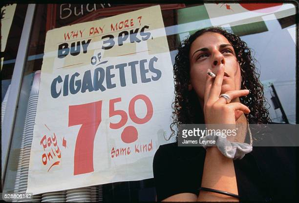 A teenage girl stands next to a sign advertising cigarettes in a New York restaurant window The sign reads 'WHY PAY MORE BUY 3 PKS OF CIGARETTES Pay...