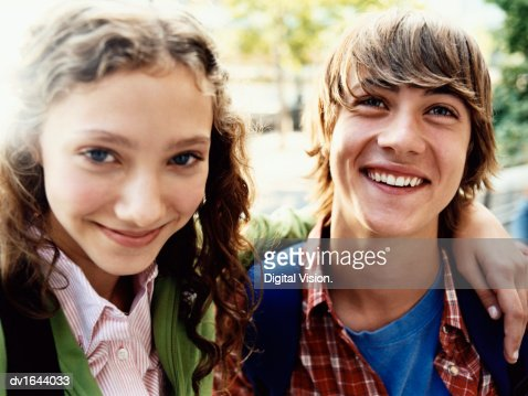 Teenage Girl Stands Smiling With Her Arm Around Her Friend : Foto de stock