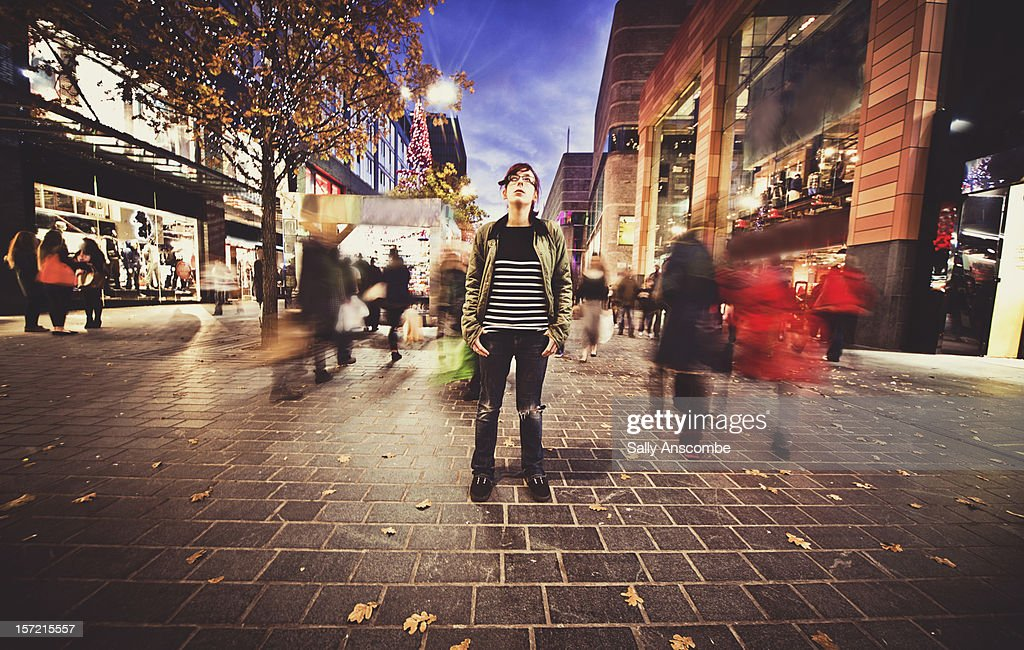 Teenage girl stood still on a busy street : Stock Photo