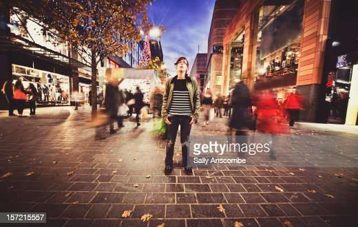 Teenage girl stood still on a busy street : Bildbanksbilder